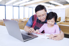 Cute student studying with teacher in class. Lovely female elementary school student studying with male teacher in the classroom, using a book and laptop on the Stock Photos