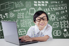 Cute Student using Laptop And Smiling at Camera. Cute little student using laptop computer while smiling at camera with scribble background on the blackboard Stock Photography
