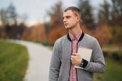 A cute student writes down his thoughts in his notebook using a pencil. The guy is holding a notebook in his hands. A cute student writes down his thoughts in Royalty Free Stock Photo