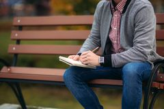 A cute student writes down his thoughts in his notebook using a pencil. Sits on bench. A cute student writes down his thoughts in his notebook using a pencil Stock Photo