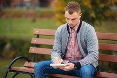 A cute student sits on the bench writes down his thoughts in his notebool using a pensil. A cute student writes down his thoughts in his notebool using a pensil Stock Images