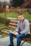 A cute student writes down his thoughts in his notebook using a pencil. Sits on bench. A cute student writes down his thoughts in his notebook using a pencil Stock Photography