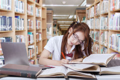 Cute student writing on the book in library Stock Image