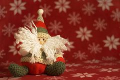 Cute Stuffed Santa Doll. Stuffed Santa puppet against a red snowflake background Royalty Free Stock Image