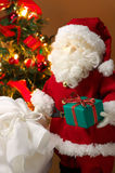 Cute stuffed toy Santa Claus giving a Christmas present. Stock Photo