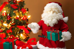 Cute stuffed toy Santa Claus giving a Christmas present. Stock Photos