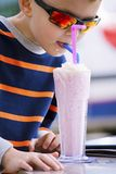 Stylish boy drinks a milkshake with ice cream. Cute stylish boy drinks a milkshake with ice cream on vacation Royalty Free Stock Photo
