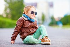 Cute stylish boy in leather jacket sitting on the road Royalty Free Stock Photography