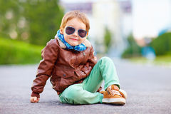 Cute stylish boy in leather jacket sitting on the road Royalty Free Stock Photos
