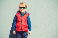 Cute stylish boy standing in front of grey wall outdoors. Royalty Free Stock Photos