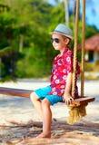 Cute stylish boy on swings on the beach Stock Image