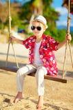 Cute stylish boy on swings at the beach Stock Image