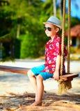 Cute stylish boy on swings on the beach Royalty Free Stock Photos