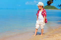Cute stylish boy walking the tropical beach Royalty Free Stock Photos