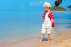 Cute stylish boy walking the tropical beach Royalty Free Stock Photos