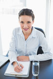 Cute stylish brunette businesswoman taking notes and looking at camera Royalty Free Stock Photography