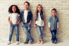 Cute stylish children. Full length portrait of cute little kids in stylish jeans clothes looking at camera and smiling, standing against white brick wall Royalty Free Stock Image