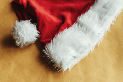 Cute stylish christmas red hat on a beautiful craft holiday wrap Stock Image