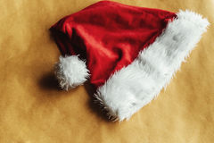 Cute stylish christmas red hat on a beautiful craft holiday wrap Stock Images