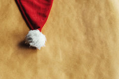 Cute stylish christmas red hat on a beautiful craft holiday wrap Royalty Free Stock Photography