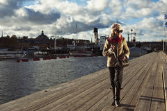 Cute stylish girl walking on pier in Stockholm Stock Photo