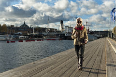 Cute stylish girl walking on pier in Stockholm Stock Photography