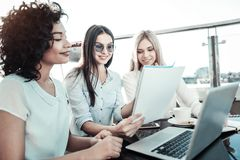 Cute stylish girls sitting and overlooking the notebook. Stock Photos