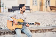 A cute stylish man with a beard sits on a concrete curb in the street and plays an acoustic guitar and smiles. The musician enjoys. His music and creates a good royalty free stock photography