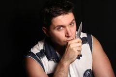 Cute stylish man with a knife in hand near face. Cute stylish man with a knife in hand near the face on black background Royalty Free Stock Photos
