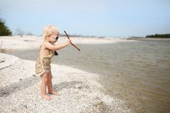 Toddler Girl Playing on Beach Throwing Sticks in the Water. A cute and stylish one year old baby girl is standing on the beach shore, throwing sticks into a royalty free stock images