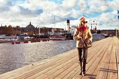 Cute stylish and trendy girl walking on pier in Stockholm. Cute smiling young stylish and trendy girl walking on pier in Stockholm on cloudy sky background royalty free stock photos