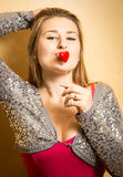 Cute stylish woman holding red heart on stick at lips Stock Images