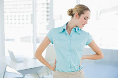 Cute suffering businesswoman holding her injured back Royalty Free Stock Photo