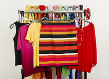 Cute summer outfits displayed on a rack. Striped skirt with matching blouses. Wardrobe with colorful summer clothes and accessories Royalty Free Stock Photo