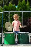 Cute sunlit toddler girl in pink posing hands behind head outdoorTwo year old cute girl learning how to play drums outdoor royalty free stock image
