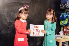 Cute sunny children standing near the blackboard with sign girls rule royalty free stock photo