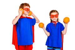 Cute super children in masks and cloaks holding oranges. On white royalty free stock photo