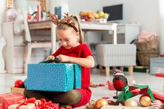 Cute super excited young girl opening large christmas present while sitting on living room floor. Candid family christmas time. stock photo