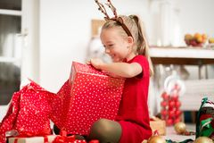 Cute super excited young girl opening large red christmas present while sitting on living room floor. Candid family christmas time stock photo