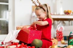 Cute super excited young girl opening large red christmas present while sitting on living room floor. Candid family christmas time stock photos