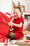 Cute super excited young girl opening large red christmas present while sitting on living room floor. Candid family christmas time royalty free stock photo