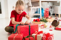 Cute super excited young girl opening large red christmas present while sitting on living room floor. Candid family christmas time stock images