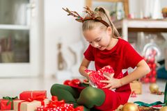 Cute super excited young girl opening large red christmas present while sitting on living room floor. Candid family christmas time. Cute super excited young girl stock photo
