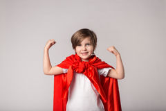 Cute superwoman kid in red cape shows her muscle Stock Photography