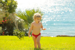 Cute surprised baby boy walks on green grass Royalty Free Stock Photos