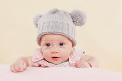 Cute surprised baby girl. Beautiful cute surprised baby girl with grey cap lying on blanket faced into the camera Stock Images