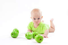 Cute surprised baby looks at green apple on a white background Royalty Free Stock Image
