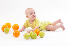 Cute surprised baby looks at green apple on a white background Stock Image