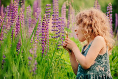 Cute surprised child girl exploring nature with loupe on summer field Stock Image