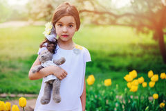 Cute surprised child girl holding teddy bear on spring walk with yellow tulips on background Royalty Free Stock Image